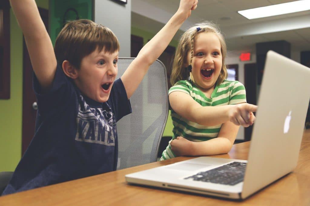 Zwei Kinder die sich vor einem Computer freuen