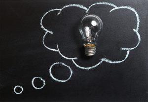 Glühbirne welche auf eine Tafel gelegt ist und von einer Gedankenwolke aus Kreide umrahmt wird.